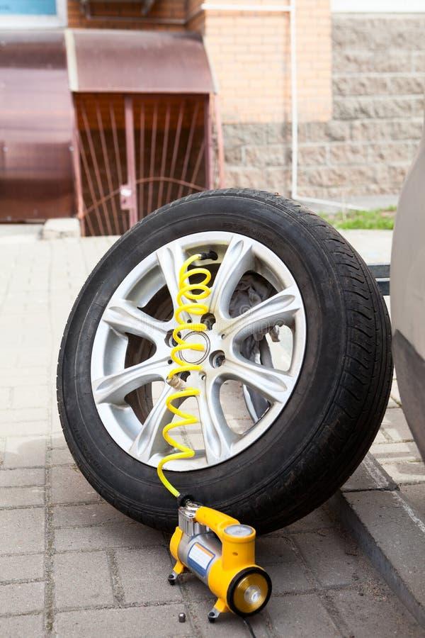 被卸下的汽车允许与轮胎的轮子外缘准备好为膨胀与气动力学的泵浦的一个轮胎 免版税库存图片