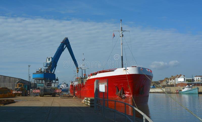 被卸载在码头边的船 图库摄影