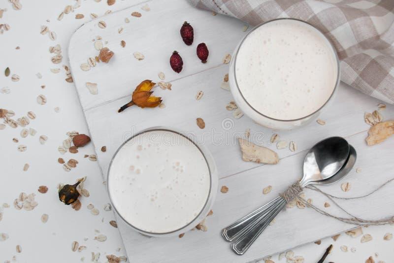 被发酵的被烘烤的牛奶饮料,Ryazhenka,俄国和乌克兰烹调,牛乳气酒,在一块玻璃的细菌发酵起始者在白色 库存照片