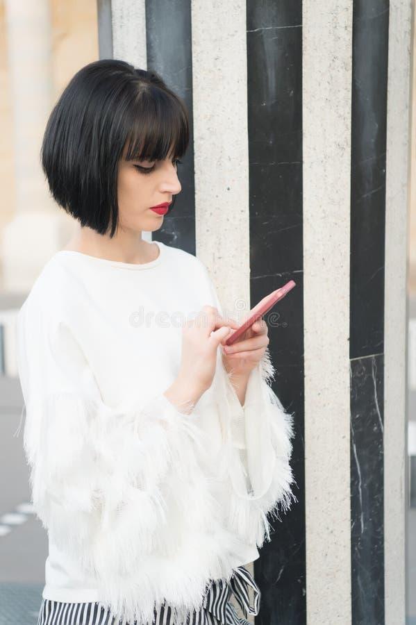 被取消的日期传送信息 女孩时兴的夫人有突然移动发型短信的智能手机室外都市背景 妇女 免版税库存图片