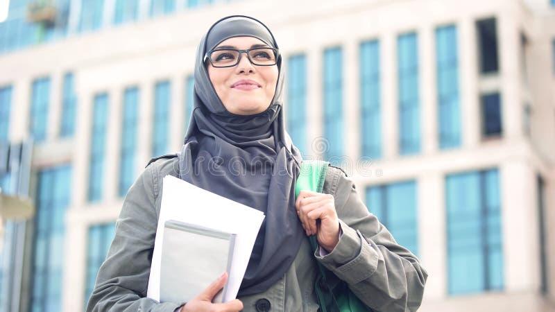 被启发的年轻女生佩带的hijab微笑,站立户外在校园里 免版税库存照片