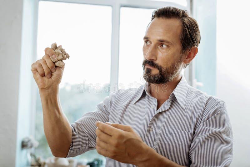 被启发的有胡子的深色头发的人感觉,当做黏土花瓶时 免版税库存照片