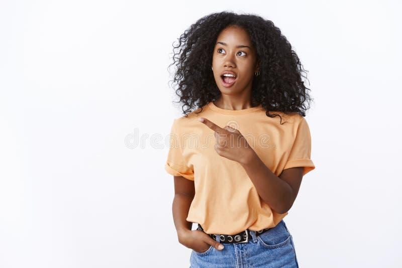 被吸引的好奇可爱的聪明的非裔美国人的女孩问问题在观光的intetested产品性能期间 库存照片