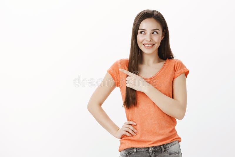 被吸引的迷人的女孩听见好奇奇怪的噪声 射击橙色T恤杉的快乐的激动的可爱的欧洲妇女 库存照片