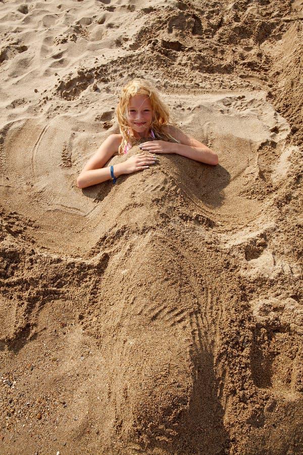 被埋没的女孩沙子下 免版税库存照片