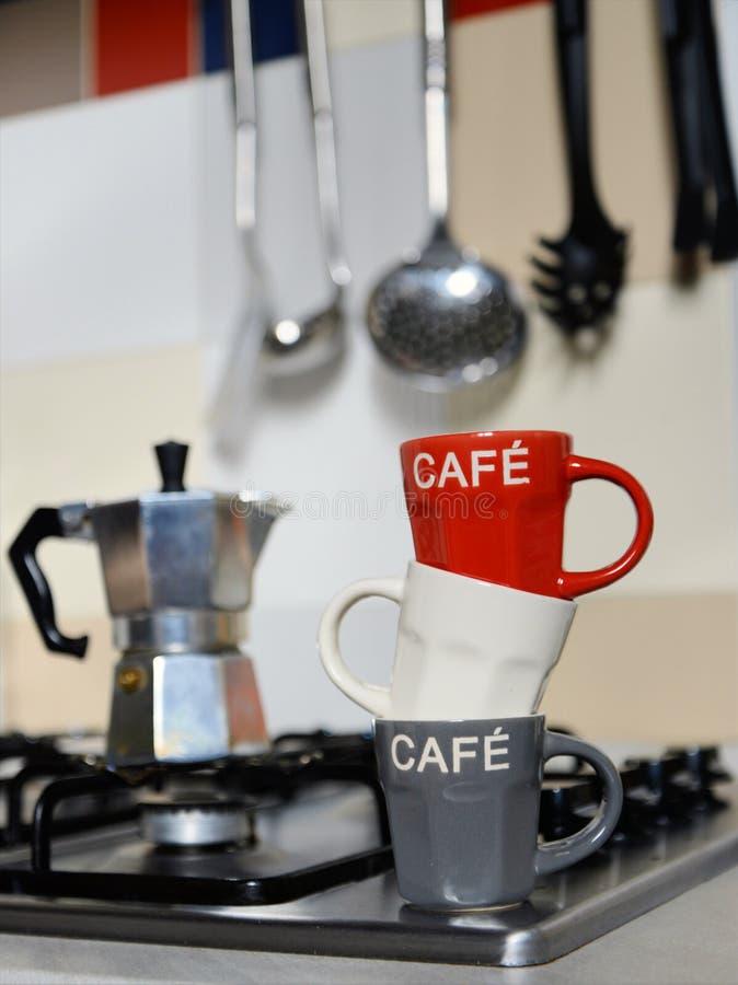 被堆积的咖啡杯和葡萄酒咖啡壶在厨灶 免版税库存照片