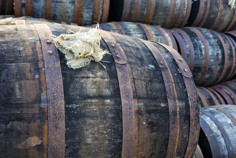 被堆积的堆老木桶和酒桶在威士忌酒蒸馏器 免版税库存照片