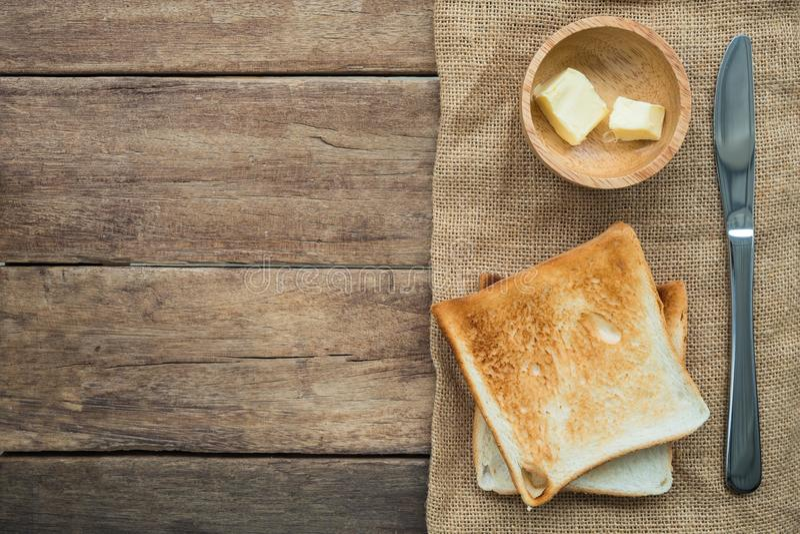 被堆积的敬酒的切片三明治面包用在木碗和不锈的刀子的黄油在木桌上的黄麻袋布料 免版税库存照片