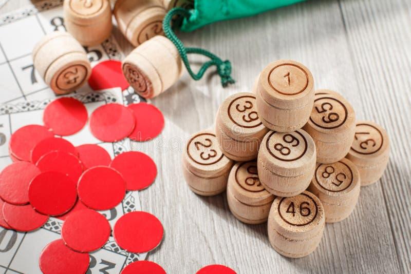 被堆积的木乐透纸牌桶、游戏卡和红色剁gam的 免版税库存照片