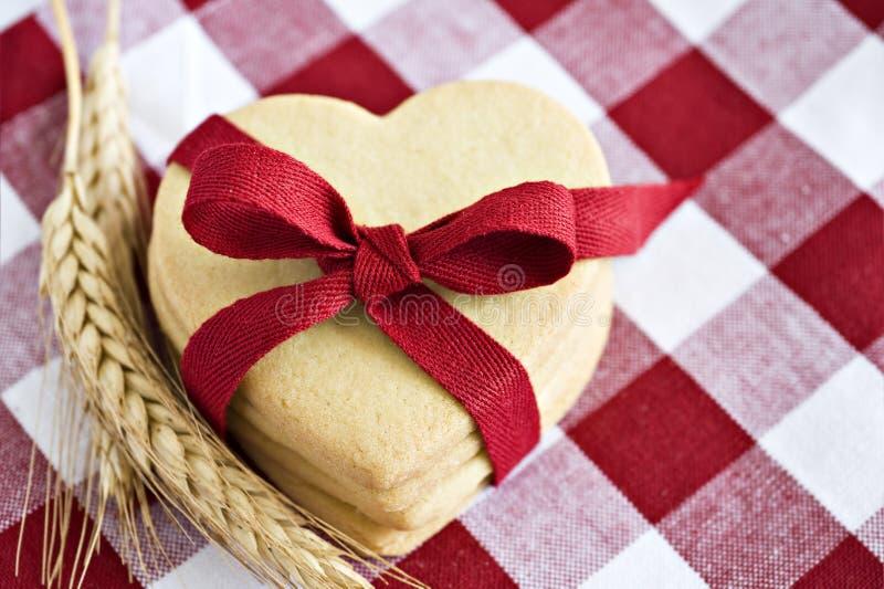 被塑造的曲奇饼重点红色丝带 免版税库存图片