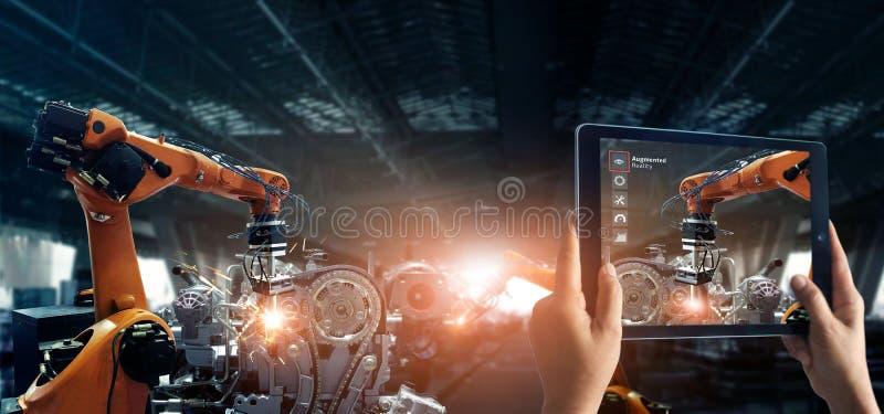 被增添的现实产业概念 举行数字片剂用途AR应用的手检查和控制自动焊接的机器人学 免版税库存照片
