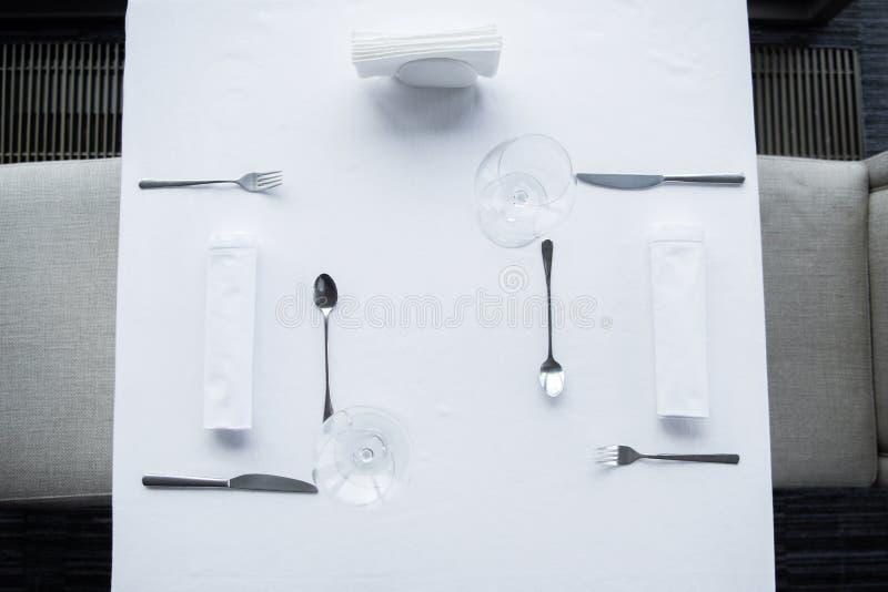 被安排的利器和葡萄酒杯顶视图在桌上与白色桌布 图库摄影