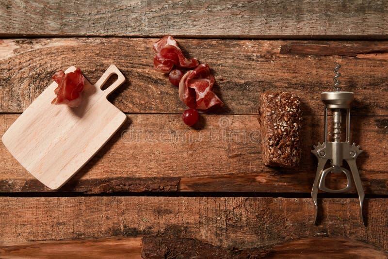 被安排的拔塞螺旋顶视图有切片的熏火腿和整粒面包在木板条 免版税库存照片