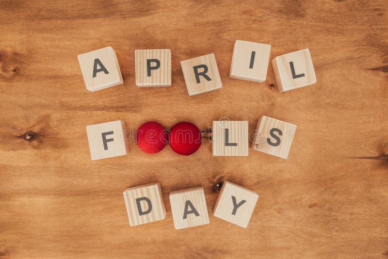 被安排的木立方体顶视图在愚人节字法在木桌面, 4月1日的 免版税库存图片