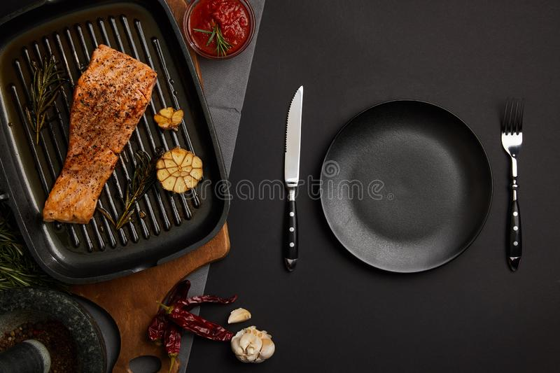 被安排的烤鲑鱼排顶视图在木切板、调味汁和利器的在黑桌面 免版税库存图片