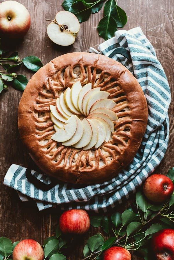 被安排的苹果饼和新鲜的苹果顶视图与绿色叶子 免版税库存图片