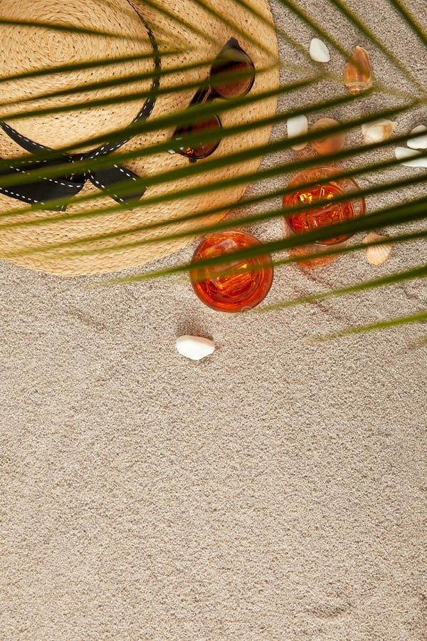被安排的草帽、太阳镜、鸡尾酒、贝壳在沙子和棕榈叶顶视图  免版税库存照片