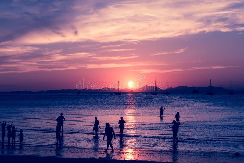 被定调子的桃红色 在海水的太阳道路  热带海岛和沙滩与很多游人剪影  享用日出 免版税库存图片