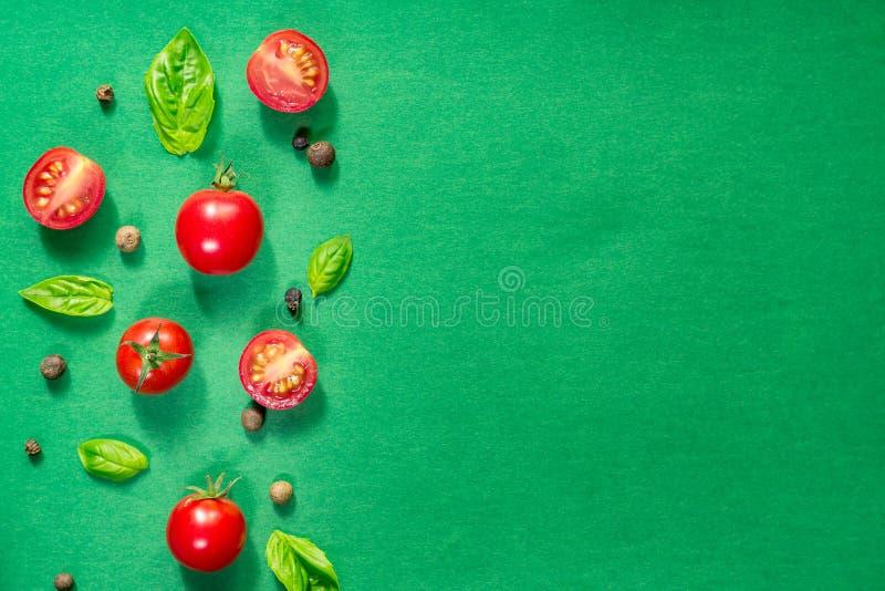 被对分的水多的西红柿和蓬蒿叶子在绿色背景 健康营养的概念 r r 库存照片