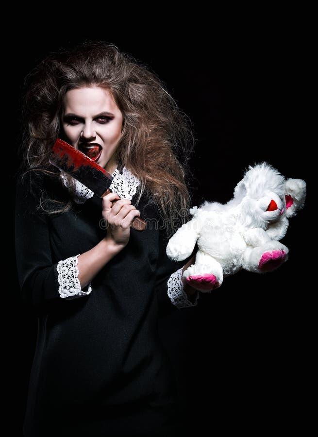 被射击的恐怖:有被撕毁的兔子玩具和血淋淋的刀子的可怕恶魔般的女孩在手上 库存照片