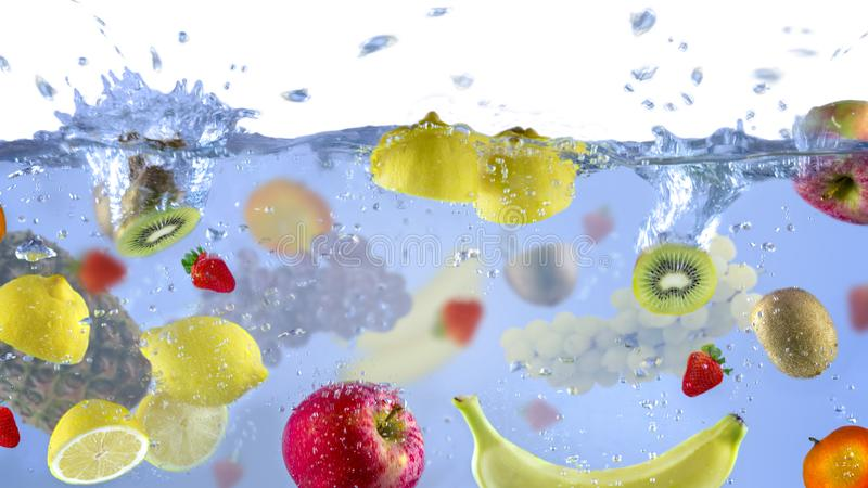 被射击的新鲜水果,他们淹没了在水族馆的水背景食物可口飞溅下 免版税库存图片