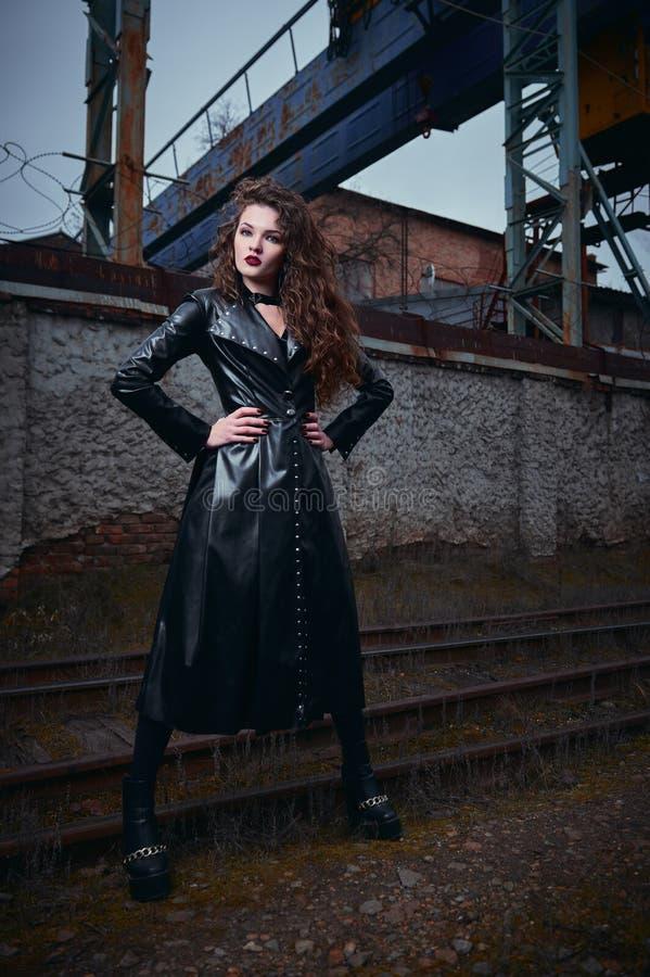 被射击的时尚:美丽的在站立在铁路工业区的皮革外套的goth女孩不拘形式的模型画象  免版税库存图片