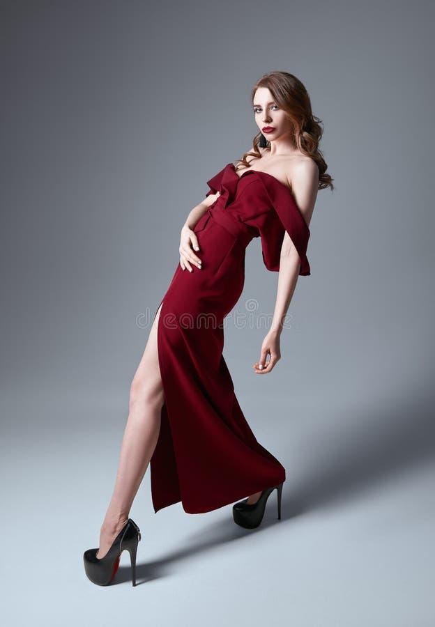 被射击的演播室时尚:肉欲的美丽的少妇画象红色礼服的 图库摄影