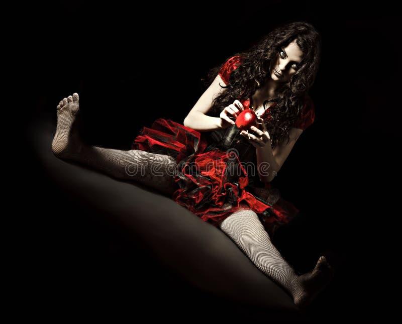 被射击的恐怖:奇怪的可怕妇女拿着苹果散布与钉子 库存照片