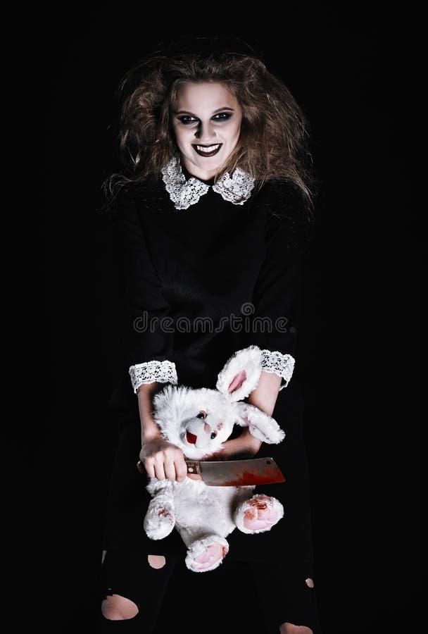 被射击的恐怖:有兔子玩具和血淋淋的砍肉刀的可怕邪恶的女孩在手上 免版税库存照片