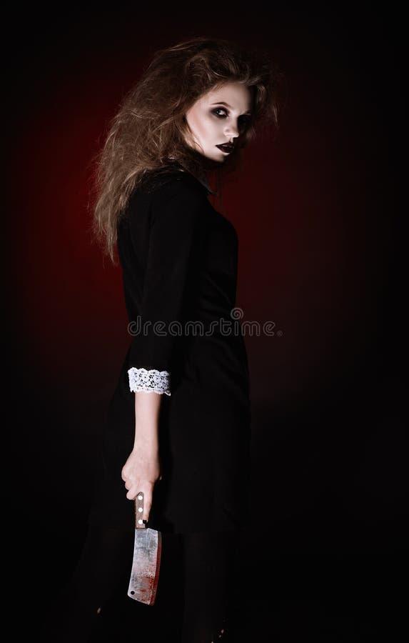 被射击的恐怖:有血淋淋的砍肉刀的可怕邪恶的女孩在手上 库存图片