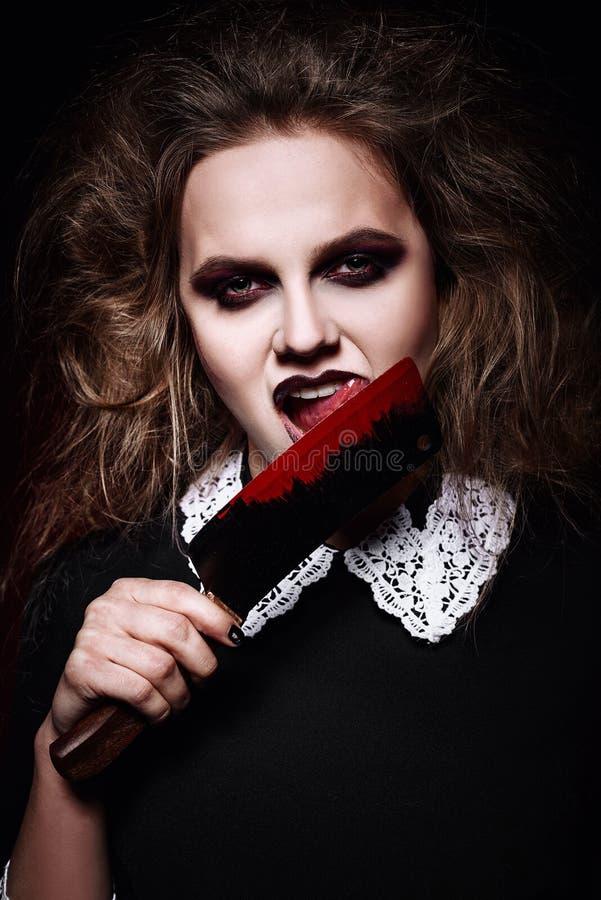 被射击的恐怖:舔血淋淋的刀子的可怕邪恶的女孩 库存照片
