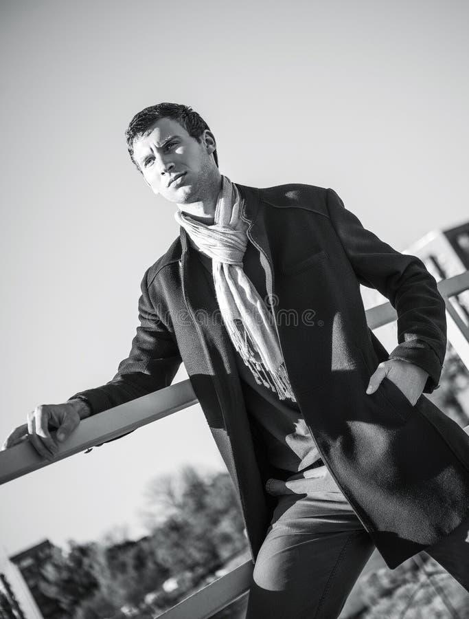 被射击的时尚:英俊的年轻人佩带的牛仔裤和外套。黑白 库存图片