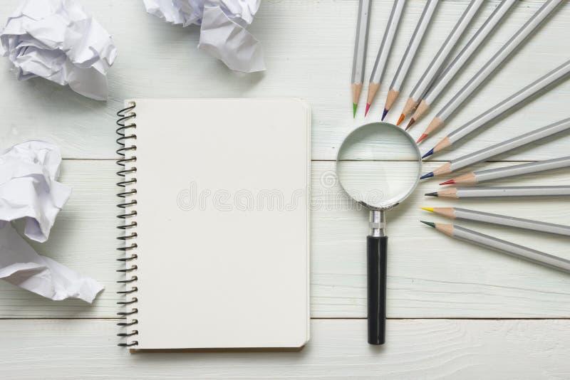 被弄皱的纸球、放大镜、铅笔和笔记本有空白的白色板料的在木桌上 创造性危机 免版税库存图片