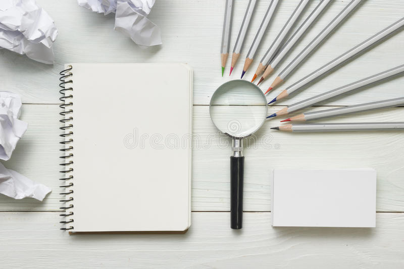 被弄皱的纸球、放大镜、铅笔和笔记本有空白的白色板料的在木桌上 创造性危机 免版税库存照片