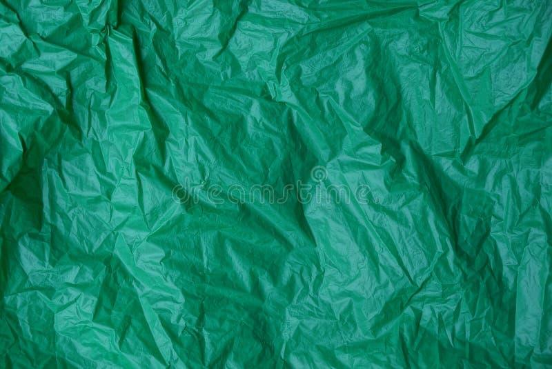 被弄皱的绿色玻璃纸片断的塑料纹理  库存图片