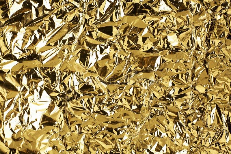 被弄皱的金黄箔发光的纹理背景,明亮的发光的金子豪华设计,金属闪烁表面 免版税图库摄影