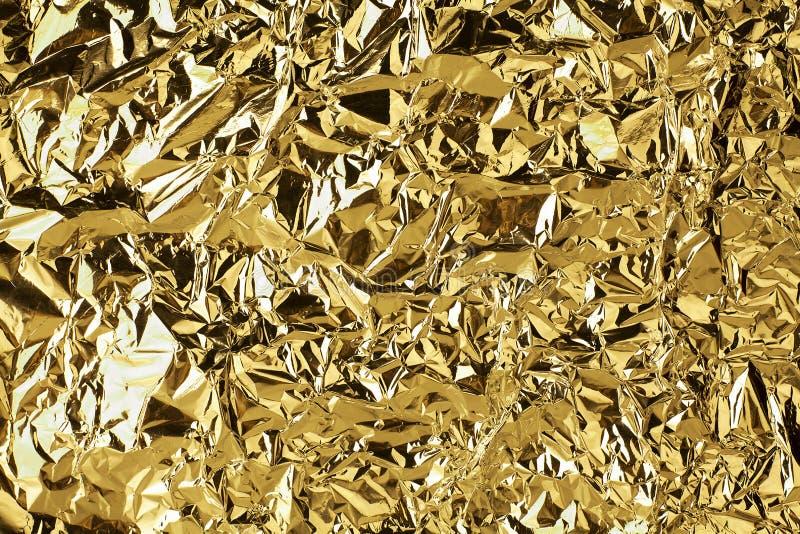 被弄皱的金黄箔发光的纹理背景,明亮的发光的金子豪华设计,金属闪烁表面 库存图片