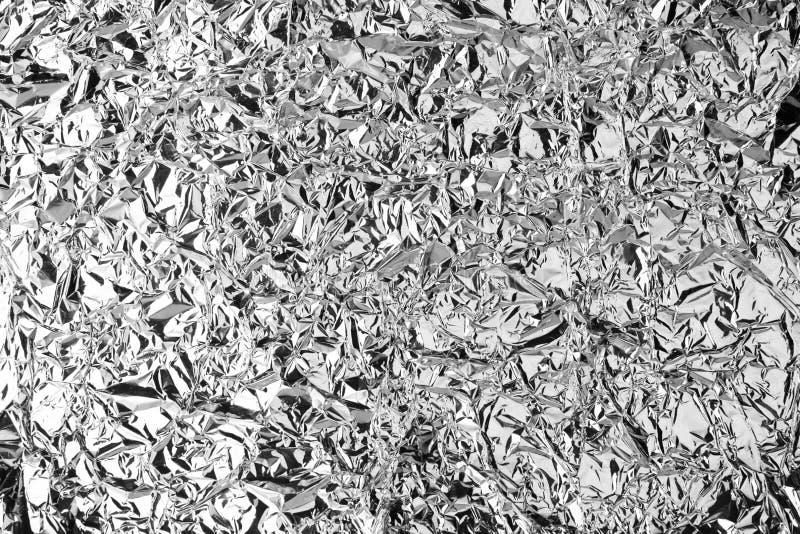 被弄皱的银箔发光的纹理背景,明亮的发光的欢乐设计,金属闪烁表面假日装饰背景 免版税图库摄影