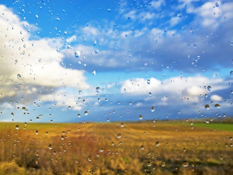 被弄脏的多云天空和培养的领域在一个车窗后与雨下落 库存图片
