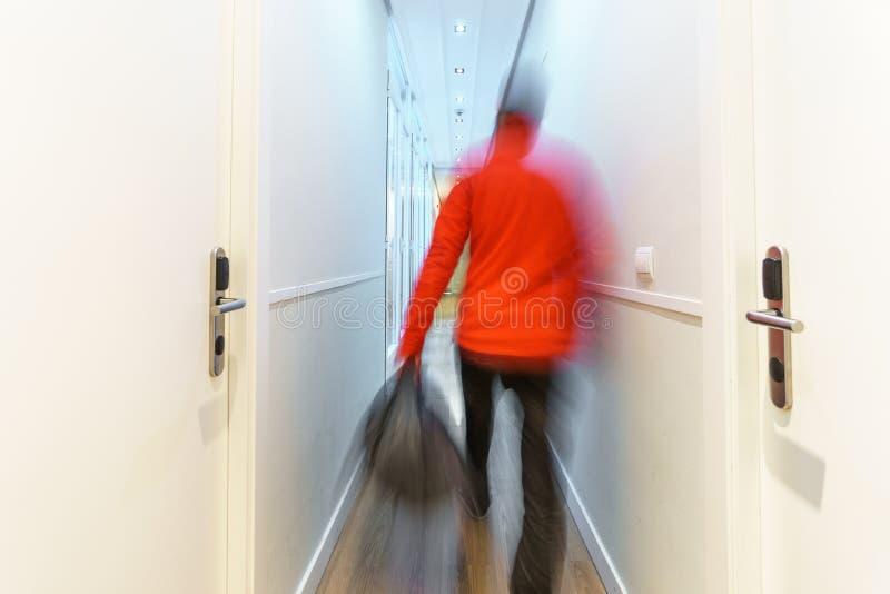 被弄脏的旅游到达对沿走廊的旅馆,长的曝光 免版税库存照片