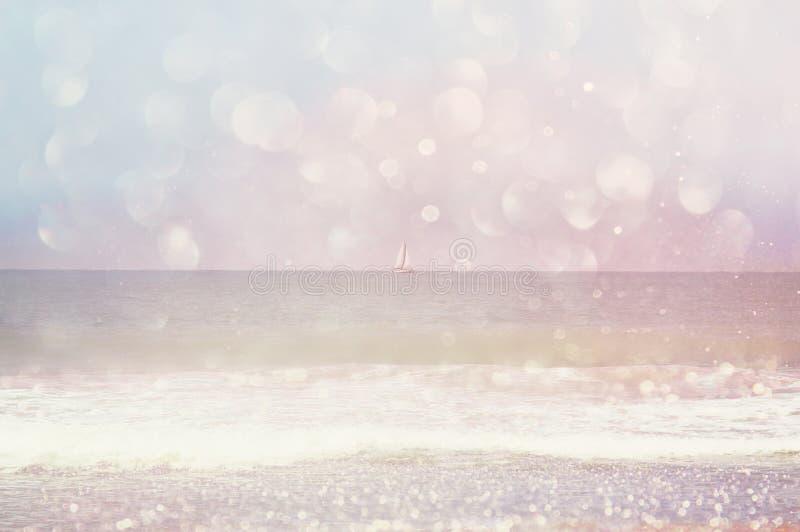被弄脏的海滩、海波浪和帆船背景在天际与bokeh点燃,葡萄酒过滤器 免版税库存照片