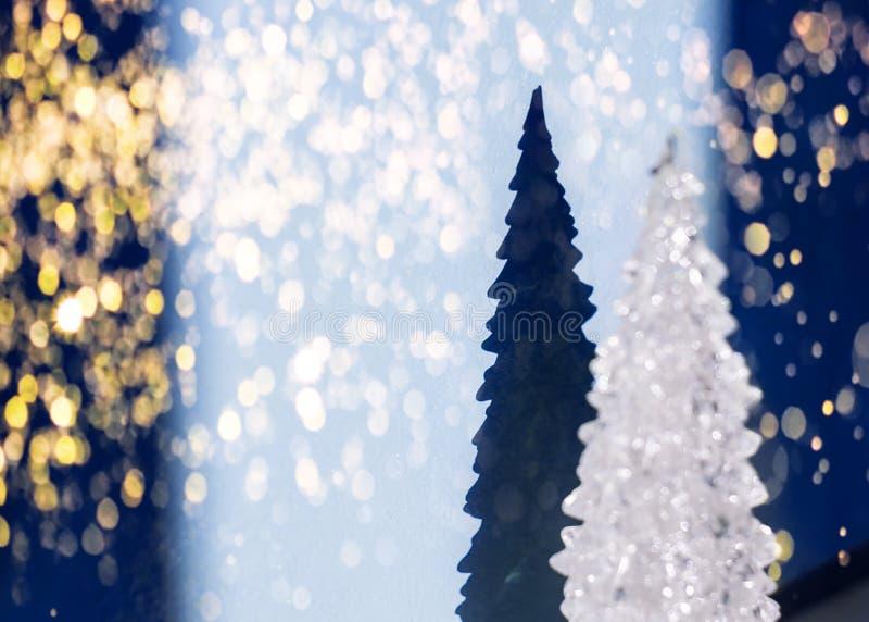 被弄脏的白色发光的纪念品圣诞树和它的剪影,在蓝色背景的阴影与庆祝闪耀的光 免版税库存图片