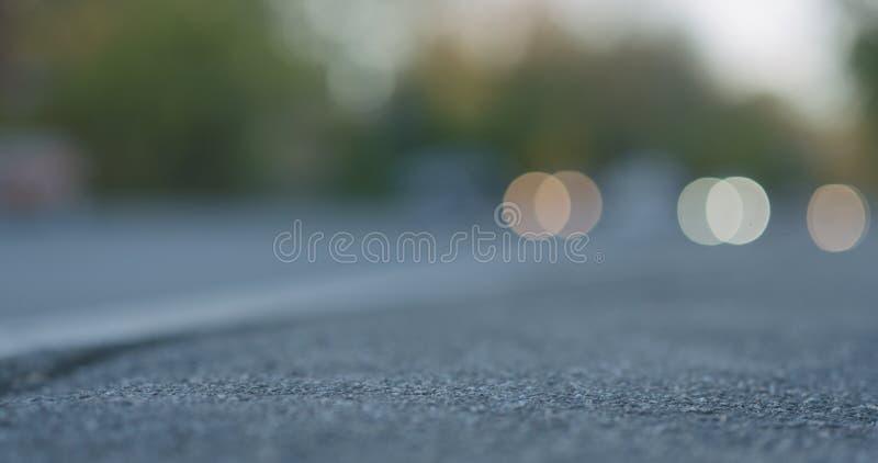 被弄脏的移动的汽车低角度射击在城市街道上的有在边路的特写镜头焦点的 免版税图库摄影