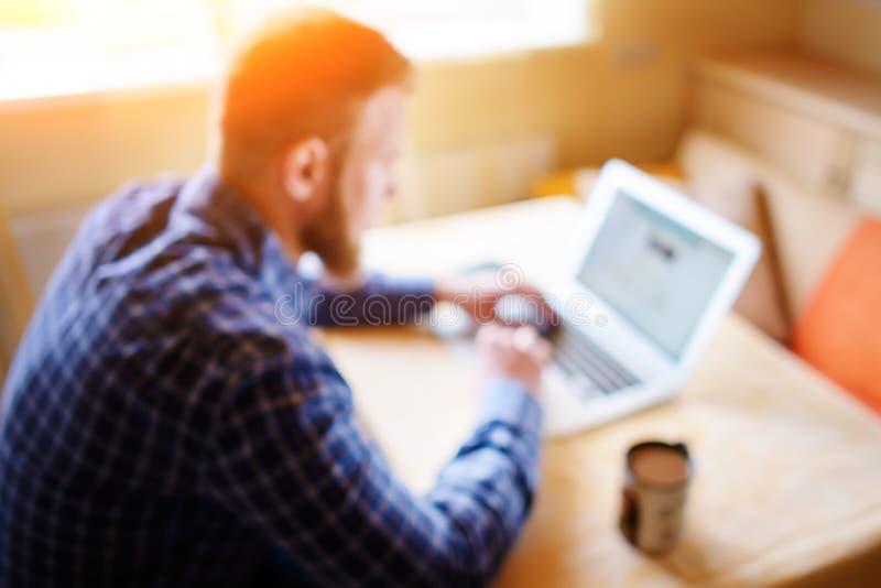 被弄脏的背景,使用膝上型计算机的商人在工作场所-后方 免版税库存图片