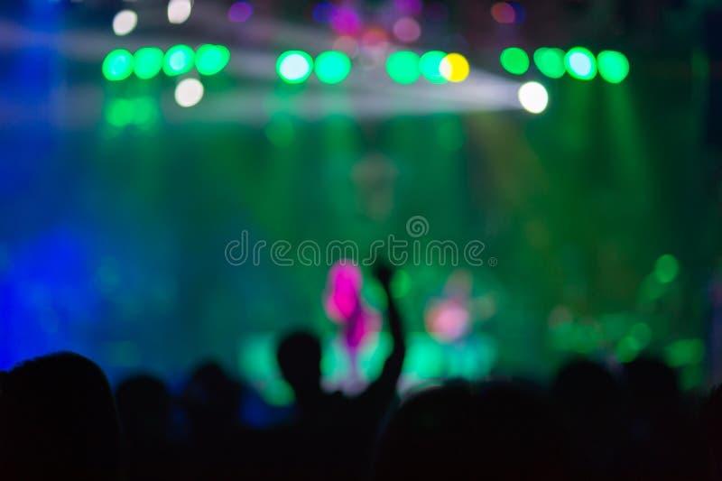 被弄脏的背景:在室外音乐会的Bokeh照明设备与欢呼的观众 库存图片