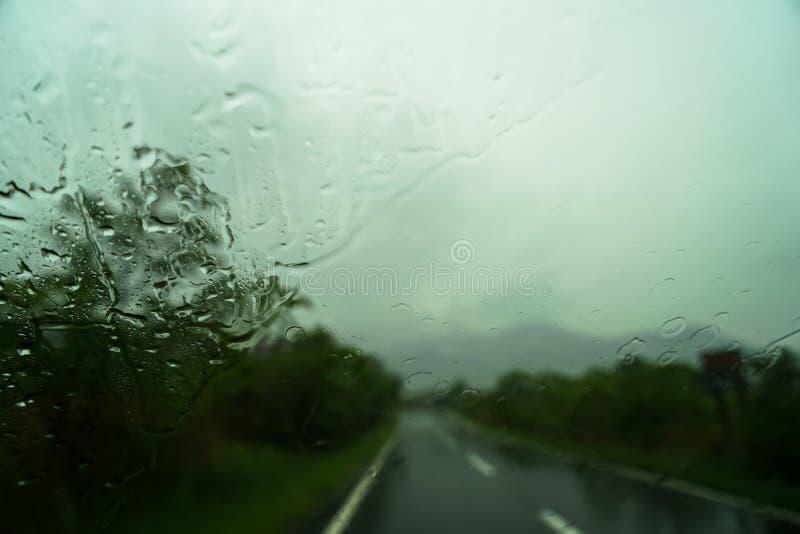 被弄脏的路线和山景看法与雨珠在汽车 免版税库存照片