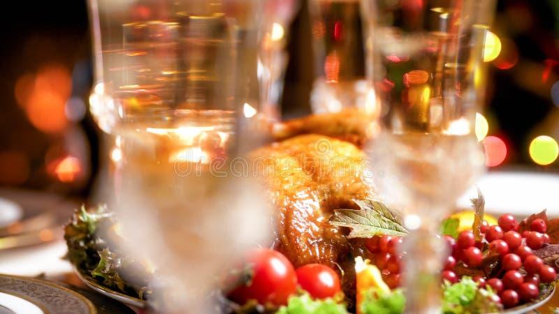 被弄脏的香槟玻璃的特写镜头图象反对烤鸡的在圣诞节dinnner 免版税库存照片