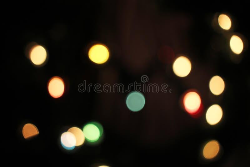 被弄脏的defocused圣诞灯光bokeh背景 五颜六色的红色黄色蓝绿色de聚焦了闪烁的样式 免版税图库摄影