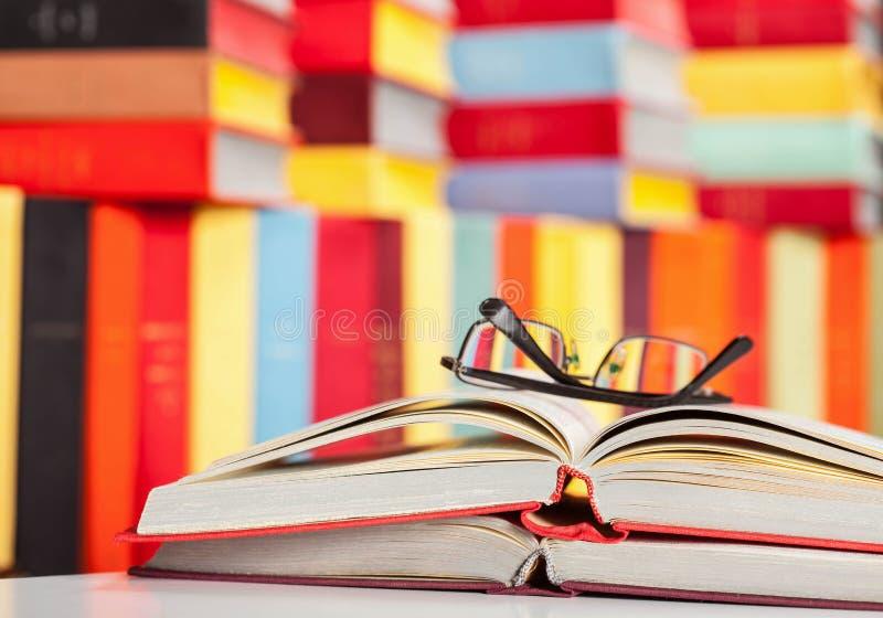 被打开的书和玻璃在色的背景 免版税库存图片