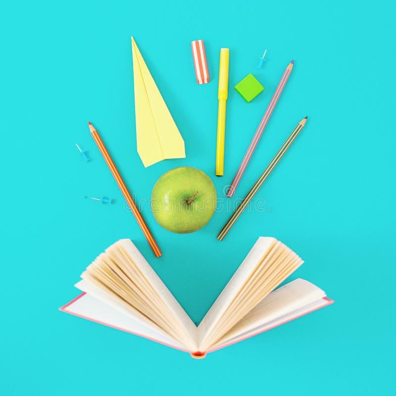 被打开的书学校用品蓝色背景顶视图最低纲领派 免版税库存照片